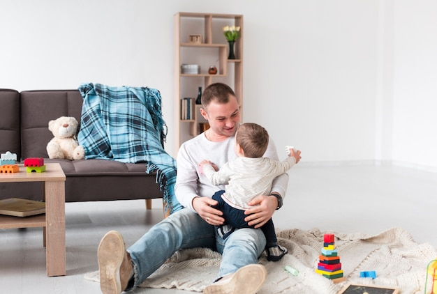Vooraanzicht van vader met baby en speelgoed thuis