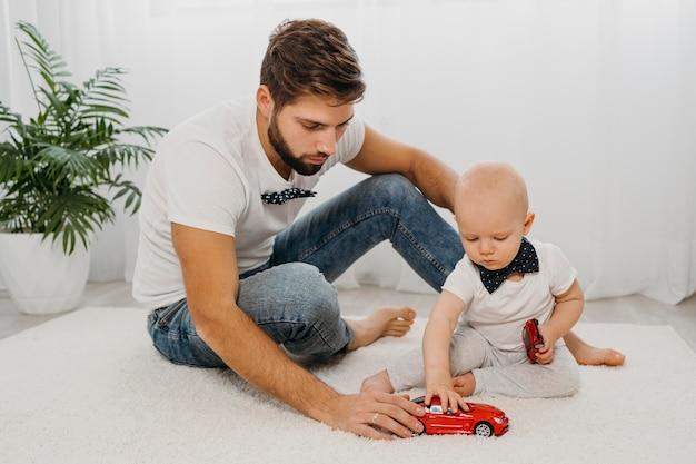 Vooraanzicht van vader spelen met baby thuis