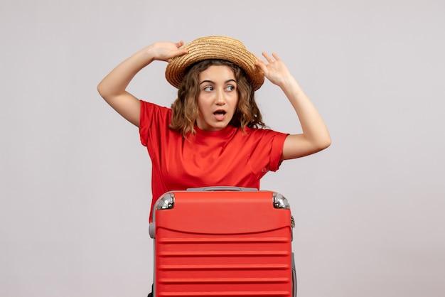 Vooraanzicht van vakantiemeisje met haar valise die haar panama houdt die zich op witte muur bevindt