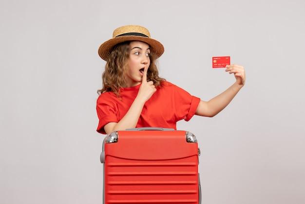 Vooraanzicht van vakantiemeisje met haar valise holdingskaart