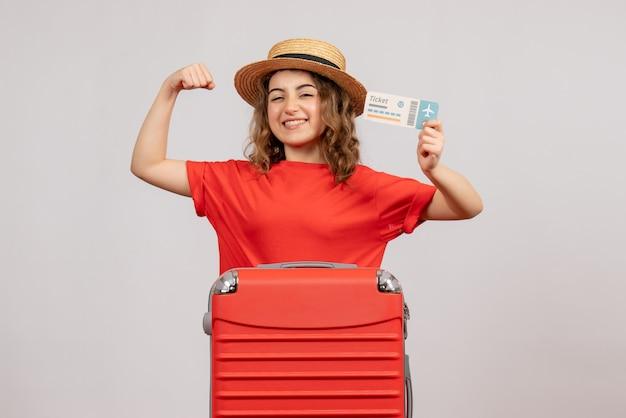 Vooraanzicht van vakantiemeisje met haar valise holdingskaartje die wapenspier tonen