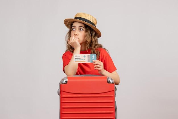 Vooraanzicht van vakantiemeisje met haar valise holdingskaartje het denken