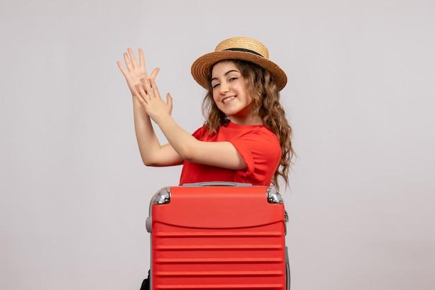 Vooraanzicht van vakantiemeisje met haar valise klappende handen die zich op witte muur bevinden