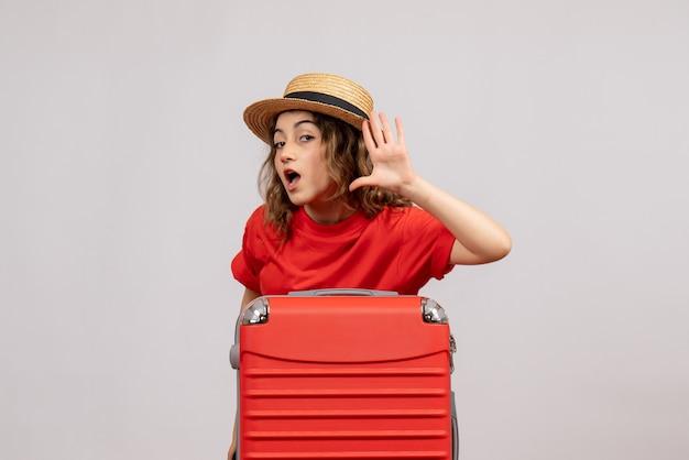 Vooraanzicht van vakantiemeisje met haar valise luisterend iets dat zich op witte muur bevindt