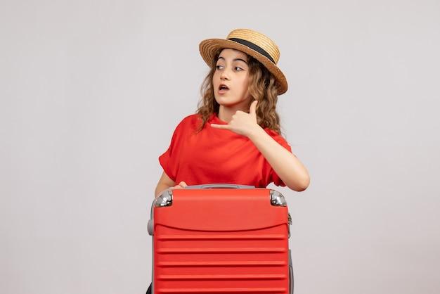 Vooraanzicht van vakantiemeisje met haar valise makend me teken die zich op witte muur bevinden