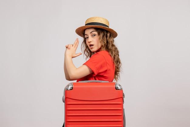 Vooraanzicht van vakantiemeisje met haar valise makend vingerkanon die zich op witte muur bevinden