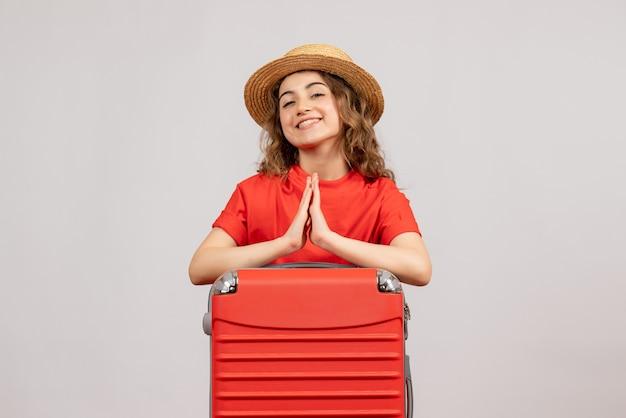 Vooraanzicht van vakantiemeisje met haar valise samen de handen ineen