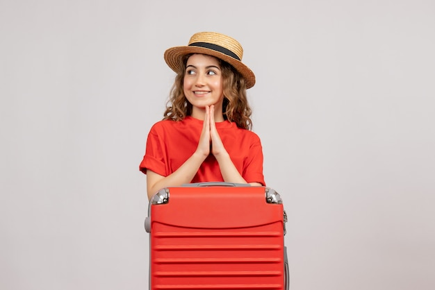 Vooraanzicht van vakantiemeisje met haar valise toetreden handen samen die zich op witte muur bevinden