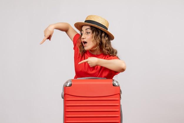 Vooraanzicht van vakantiemeisje met haar valise wijzend op iets dat zich op wit geïsoleerde muur bevindt