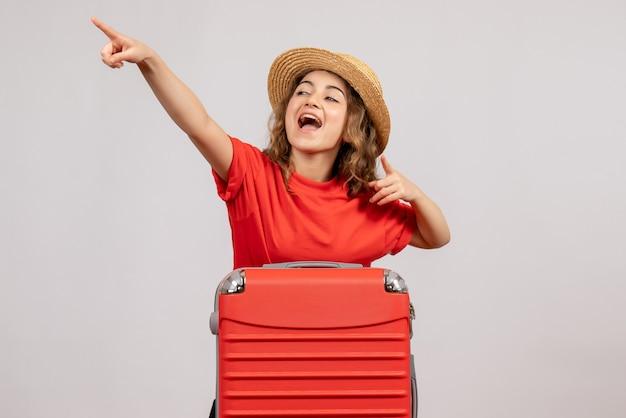 Vooraanzicht van vakantiemeisje met haar valise wijzend op iets dat zich op witte muur bevindt
