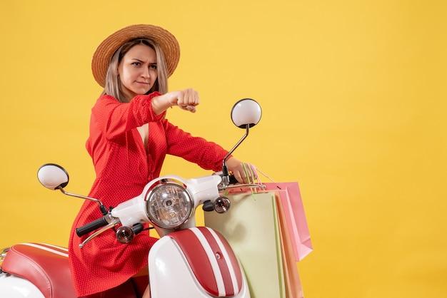 Vooraanzicht van vastberaden vrouw in rode jurk op bromfiets met boodschappentassen