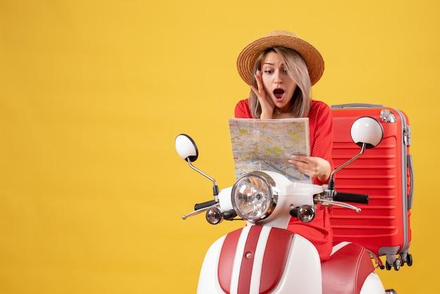 Vooraanzicht van verbaasd mooi meisje op bromfiets met rode koffer met kaart