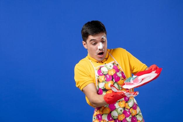 Vooraanzicht van verbaasde huishoudster met schuim op zijn gezicht met plaat met schuim op blauwe muur