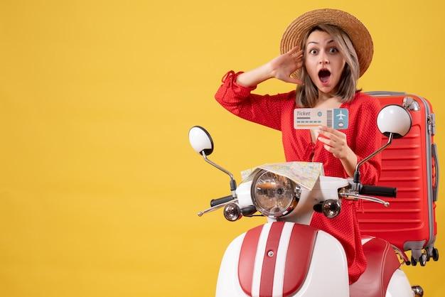 Vooraanzicht van verbaasde jonge dame in rode jurk met kaartje op bromfiets