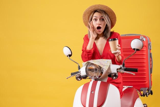 Vooraanzicht van verbaasde jonge dame in rode jurk met koffiekopje in de buurt van bromfiets