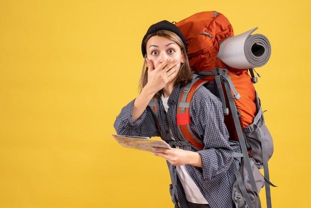 Vooraanzicht van verbaasde jonge reiziger met de kaart van de rugzakholding