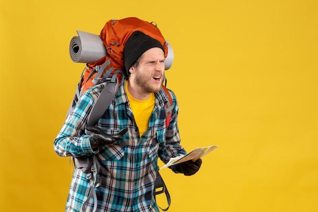 Vooraanzicht van verbaasde jonge toerist met lederen handschoenen en rugzak met kaart