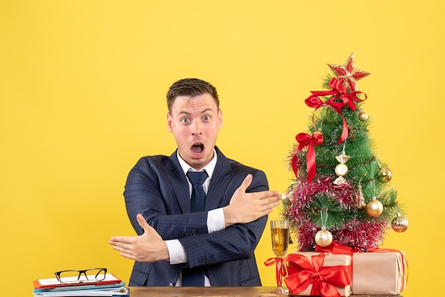 Vooraanzicht van verbaasde man met aanwijzingen zittend aan de tafel in de buurt van kerstboom en presenteert op gele muur