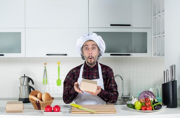 Vooraanzicht van verbaasde mannelijke chef-kok met doos in de keuken