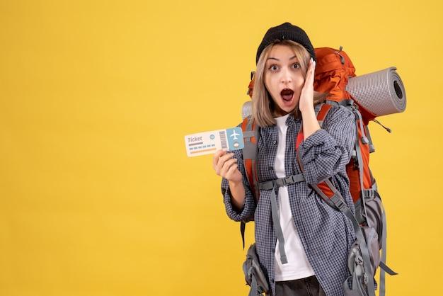 Vooraanzicht van verbaasde reizigersvrouw met het kaartje van de rugzakholding