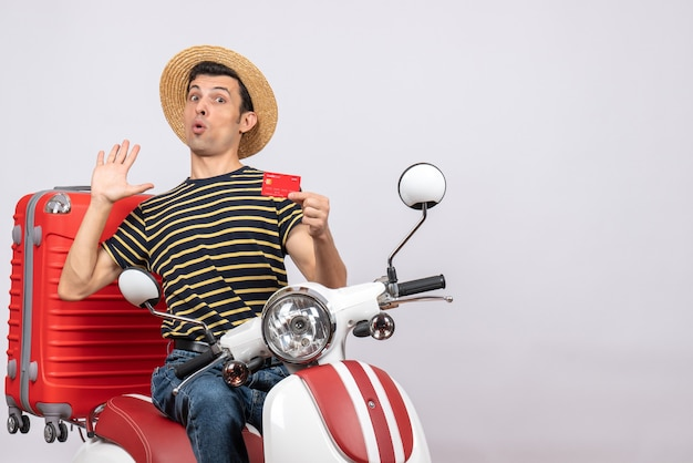 Vooraanzicht van verbijsterde jonge man met strooien hoed op bromfiets met creditcard