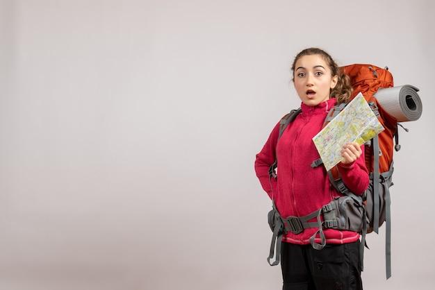 Vooraanzicht van verbijsterde jonge reiziger die met grote rugzak kaart steunt