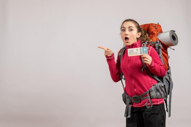 Vooraanzicht van verbijsterde jonge reiziger die met grote rugzak reisticket steunt