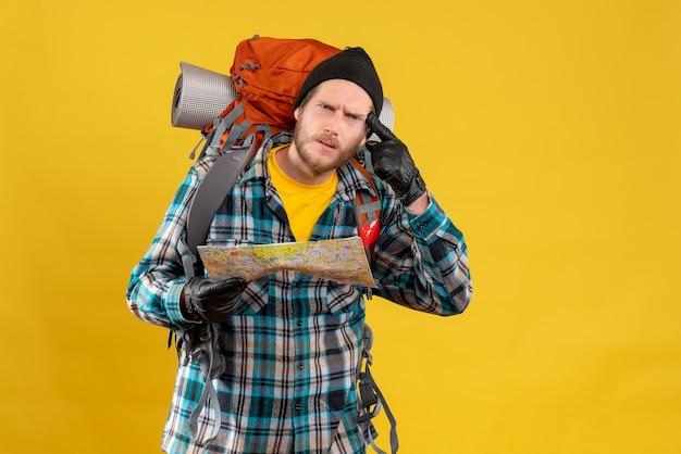 Vooraanzicht van verbijsterde jonge toerist met lederen handschoenen en rugzak met kaart