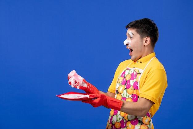 Vooraanzicht van verheugde huishoudster met schuim op zijn gezicht die plaat op blauwe muur wast