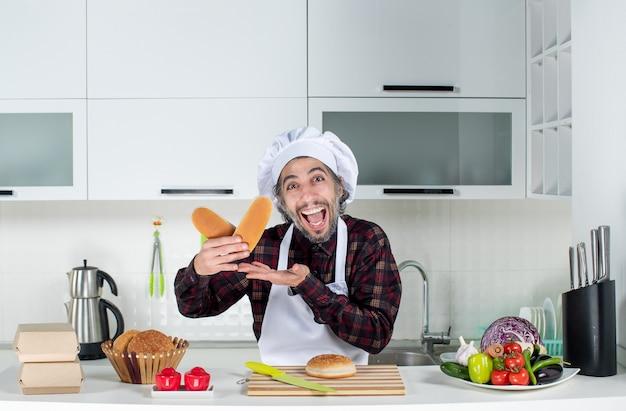 Vooraanzicht van verheugde mannelijke chef-kok die brood in de keuken houdt
