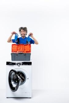 Vooraanzicht van verheugde reparateur die handschoenen achter wasmachine op witte muur houdt