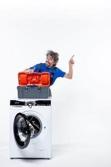 Vooraanzicht van verheugde reparateur wijzend naar rechts achter wasmachine op witte muur