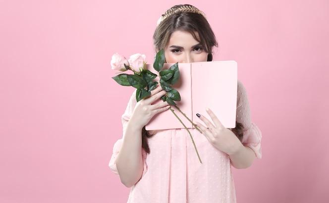 Vooraanzicht van verlegen vrouw met rozen en boek