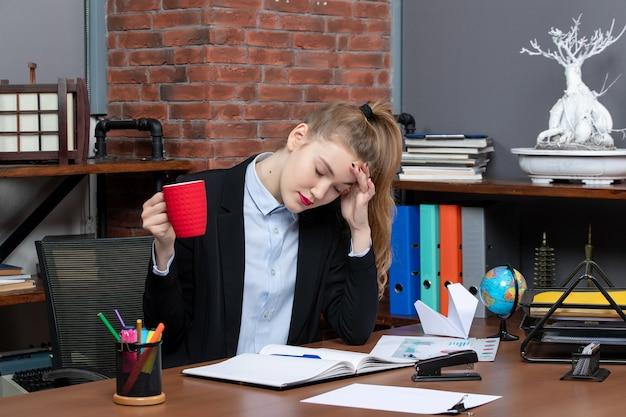 Vooraanzicht van vermoeide jonge vrouw die aan een tafel zit en een rode kop vasthoudt op kantoor