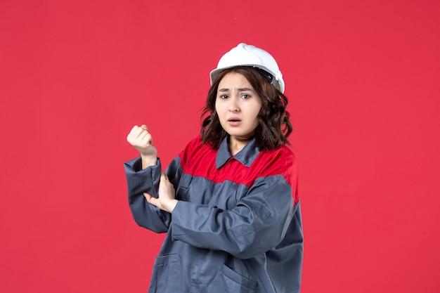 Vooraanzicht van verontrustende vrouwelijke bouwer in uniform met harde hoed en lijdend aan handpijn op geïsoleerde rode achtergrond