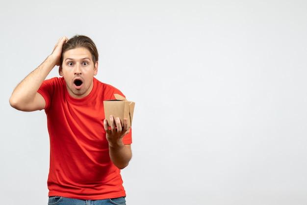 Vooraanzicht van verrast geschokt jonge kerel in rode blouse met kleine doos op witte achtergrond