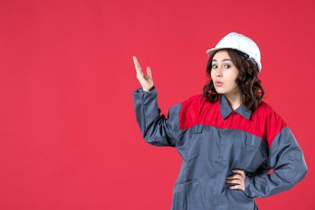 Vooraanzicht van verraste geschokte vrouwelijke bouwer in uniform met harde hoed en omhoog gericht op geïsoleerde rode achtergrond