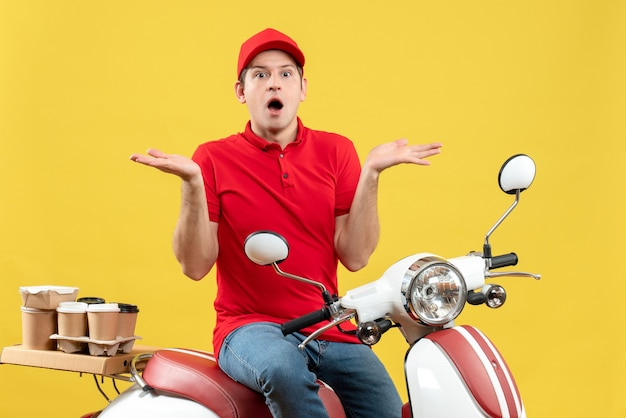 Vooraanzicht van verraste jonge kerel die rode blouse en hoed draagt die orden levert die beide kanten op gele achtergrond richten