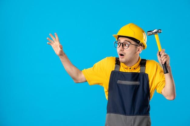 Vooraanzicht van verraste mannelijke bouwer in uniform met hamer in zijn handen op blauw
