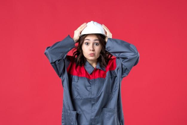 Vooraanzicht van verraste vrouwelijke bouwer in uniform met helm op geïsoleerde rode achtergrond