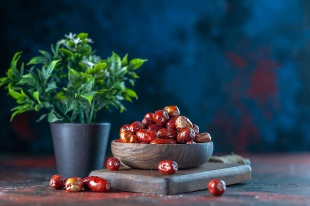 Vooraanzicht van vers rauw zilverbessenfruit in een kom op een houten snijplank en bloempot op de achtergrond van mixkleuren