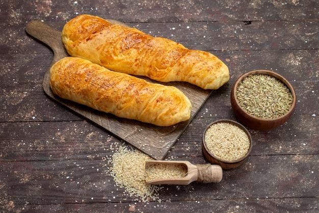 Vooraanzicht van vers smakelijk gebakje lang broodje gevormd gebakje met kruiden op het bruine houten bureau