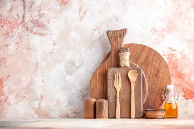Vooraanzicht van verschillende snijplanken houten lepels kleine oliefles aan de linkerkant op kleurrijk oppervlak