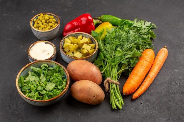 Vooraanzicht van verse groenten met groenen op een donkere ondergrond