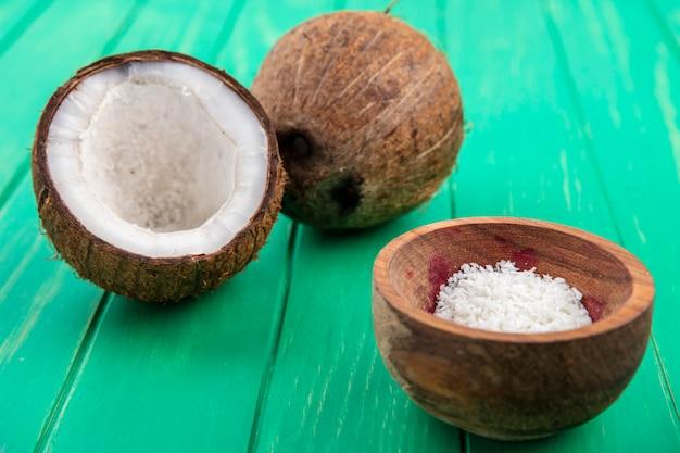 Vooraanzicht van verse kokosnoten met kokos poeder op een houten kom op groene ondergrond