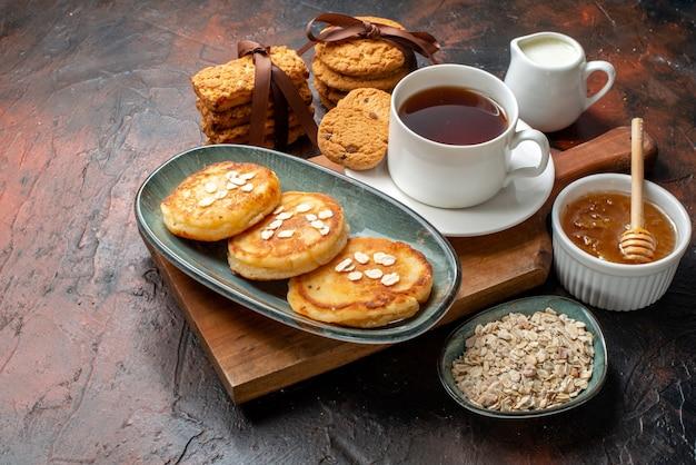 Vooraanzicht van verse pannenkoeken een kopje zwarte thee op een houten snijplank honing gestapelde koekjes melk op een donker oppervlak