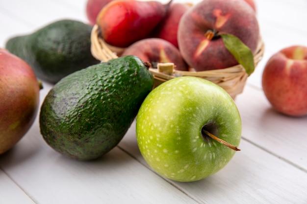 Vooraanzicht van verse perziken op een emmer met avocado en appel op een witte ondergrond