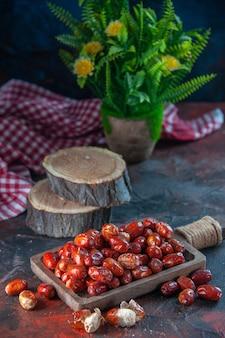 Vooraanzicht van verse rauwe zilverbessenvruchten aan de binnen- en buitenkant van een houten dienblad, bloempot, rode gestripte handdoek op de achtergrond van de mixkleuren