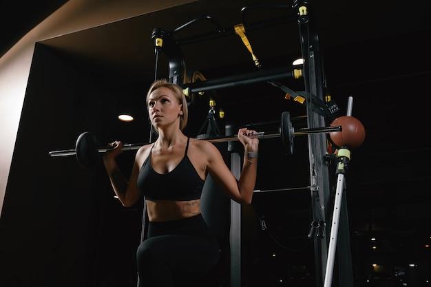 Vooraanzicht van vertrouwen jonge blonde vrouw doet gewichtheffen training aantrekkelijke jonge vrouw tillen gewicht op zoek naar voren sterk getrainde lichaamsvorm armen borst benen.