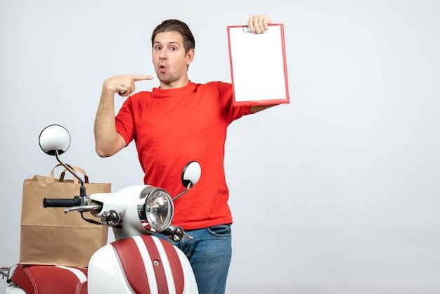 Vooraanzicht van verwarde bezorger in rode uniform staande in de buurt van scooter met document wijst naar zichzelf op witte achtergrond
